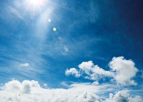 日光が降り注ぐ青空と白い雲のA4サイズ背景素材